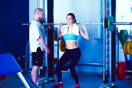 Mujer hermosa en el gimnasio haciendo ejercicio con su entrenador. Mujer hermosa. Gimnasio Foto de archivo