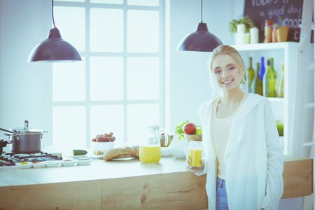 Attractive woman holding a glass of orange juice while standing in the kitchen Stockfoto