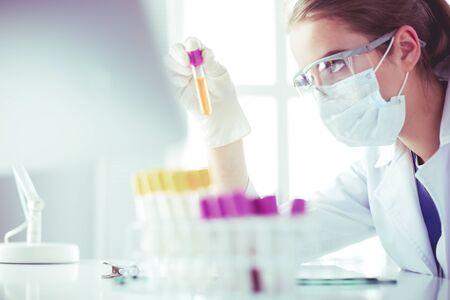 Vrouw onderzoeker is omringd door medische flesjes en kolven, geïsoleerd op wit