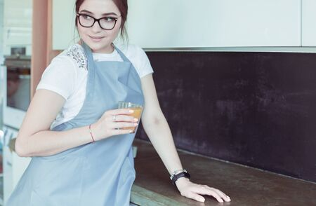 Attractive woman holding a glass of orange juice while standing in the kitchen. Stockfoto
