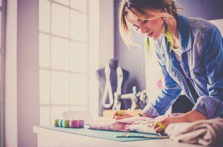 Fashion designer woman working on her designs in the studio