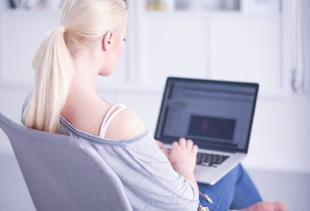 Beautiful young brunette woman at home sitting on sofa or settee using her laptop computer