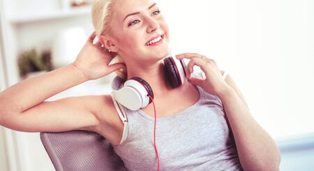 Young beautiful woman at home sitting on sofa and listening music 写真素材 - 128831517