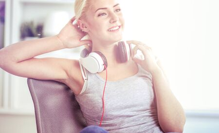 Young beautiful woman at home sitting on sofa and listening music 写真素材 - 128831520