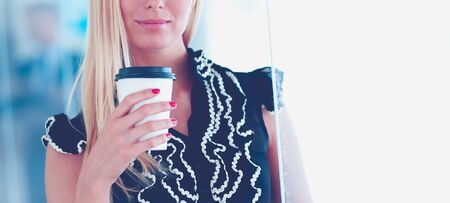 A young woman having coffee in office