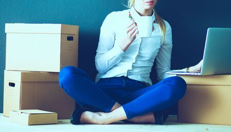 Woman sitting on the floor near a boxes with laptop . Businesswoman Stockfoto