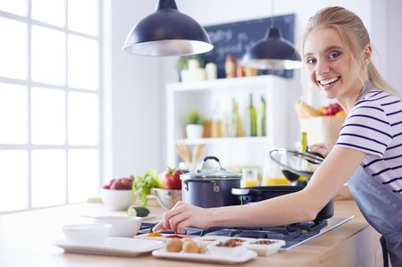 Beautiful young woman cooking in kitchen at home