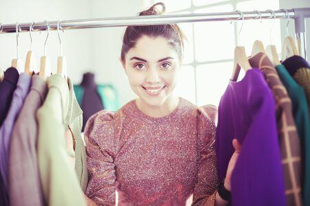 Beautiful young stylist near rack with hangers Stok Fotoğraf - 129233878