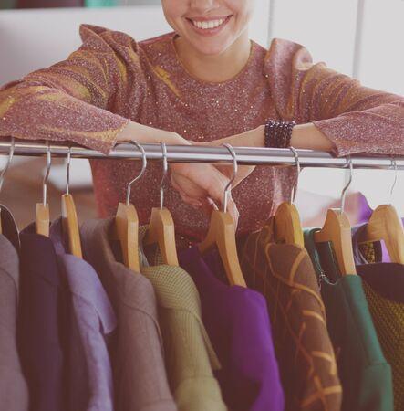 Beautiful young stylist near rack with hangers Stok Fotoğraf - 129233904