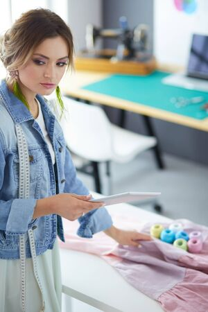 Fashion designer woman working with ipad on her designs in the studio Stockfoto