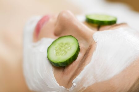 Beautiful young woman receiving facial mask of cucumber in beauty salon
