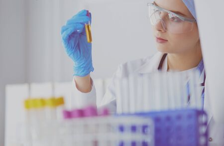A female medical or scientific researcher or woman doctor looking at a test tube of clear solution in a laboratory Zdjęcie Seryjne