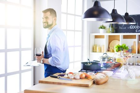 Man following recipe on digital tablet and cooking tasty and healthy food in kitchen at home Stockfoto