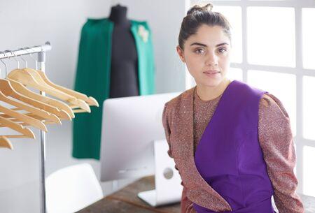 Beautiful young stylist near rack with hangers Stok Fotoğraf - 129234031