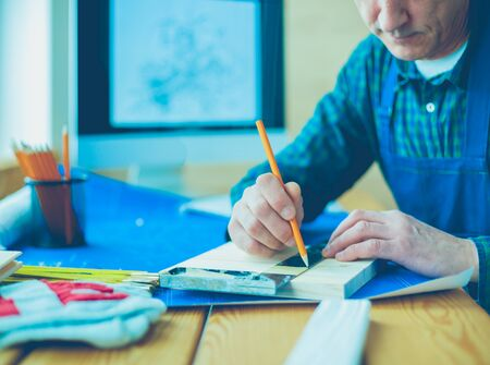 Architect working on drawing table in office Imagens