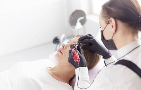Young woman undergoing procedure of eyebrow permanent makeup in beauty salon Imagens