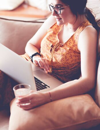 Young woman sitting on couch working on laptop computer at home