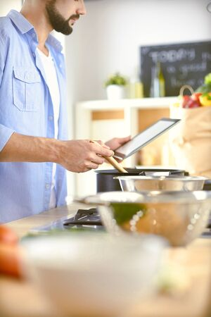 Man following recipe on digital tablet and cooking tasty and healthy food in kitchen at home Imagens