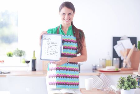 Young woman in the apron is cooking in the kitchen
