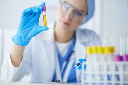 Laboratory assistant woman analyzing a blood sample Stock Photo