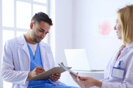 Handsome doctor is talking with young female doctor and making notes while sitting in his office. Stockfoto