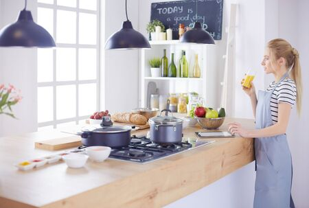 Attractive woman holding a glass of orange juice while standing in the kitchen 스톡 콘텐츠