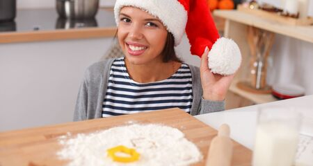 Woman in santa hat making christmas cookies in the kitchen 写真素材