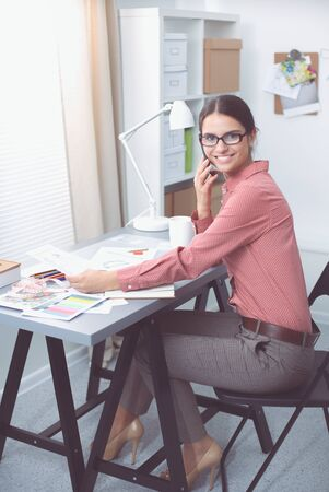 Portrait of attractive female fashion designer sitting at office desk, smiling