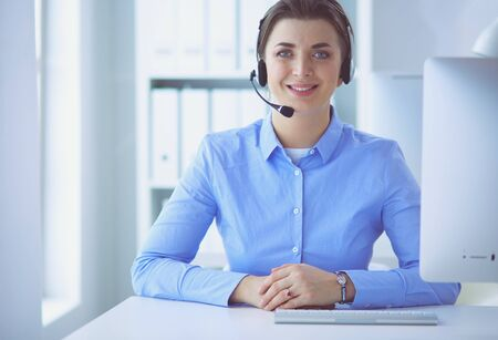 Serious pretty young woman working as support phone operator with headset in office