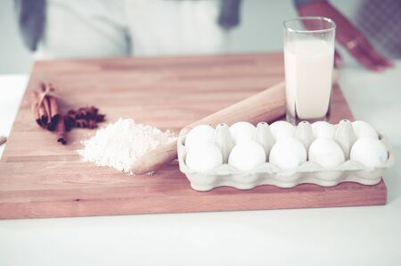 Baking background with eggs, raw eggs in a dish, eggshells, flour, rolling pin and whisk on a wooden background Imagens