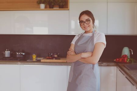 Portrait of young woman standing with arms crossed against kitchen background Stock fotó