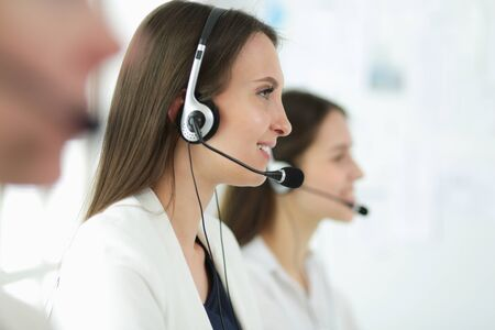 Smiling businesswoman or helpline operator with headset and computer at office