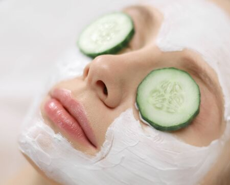 Beautiful young woman receiving facial mask of cucumber in beauty salon 스톡 콘텐츠 - 129967614