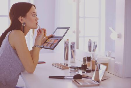 Brunette woman applying make up for a evening date in front of a mirror