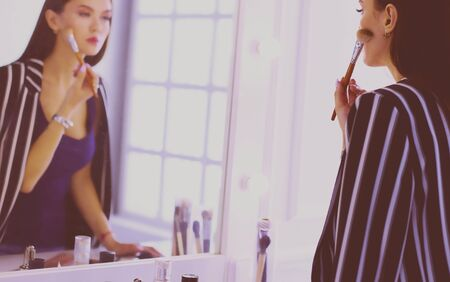 Beautiful girl looking in the mirror and applying cosmetic with a big brush 스톡 콘텐츠