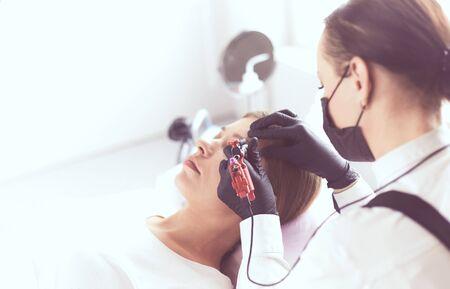 Young woman undergoing procedure of eyebrow permanent makeup in beauty salon 写真素材