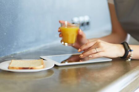 Young woman with orange juice and tablet in kitchen Stock fotó
