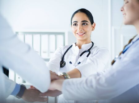 Doctors and nurses in a medical team stacking hands Фото со стока - 131394370