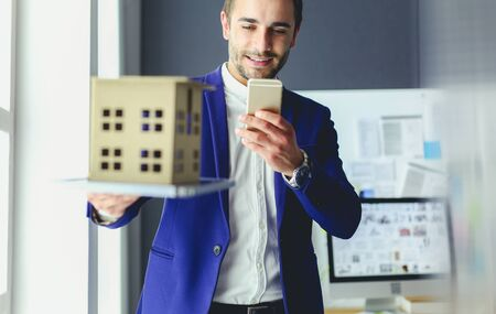 Businessman holding house miniature on hand standing in office. Stok Fotoğraf