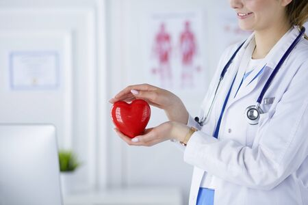 Female doctor with stethoscope holding heart, on light background.