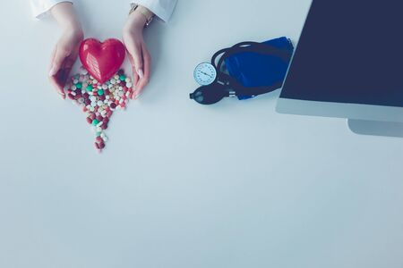 Cardiologist with red heart and stethoscope at table.