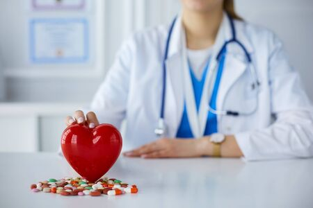 Doctor in white coat with stethoscope holding pills and plastic heart isolated on white.