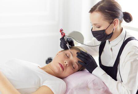 Young woman undergoing procedure of eyebrow permanent makeup in beauty salon.