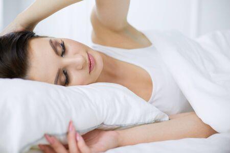 Young beautiful woman lying in bed Banco de Imagens
