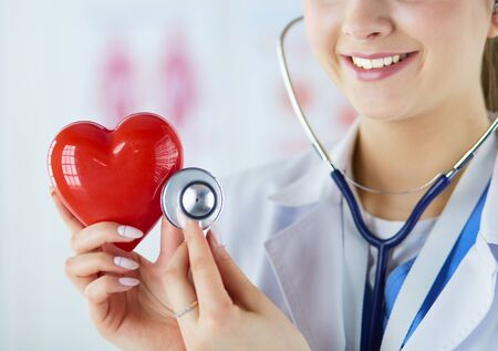 A doctor with stethoscope examining red heart, isolated on white. Stock Photo