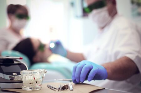 Senior male dentist adjust searchlight before starting work.