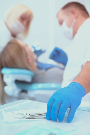 Detail of hand holding dental tools in dental clinic. Dentist Concept. Imagens