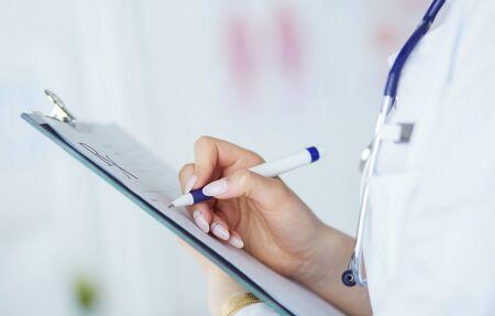 Ärztin hält leeres Rezeptdokument. Büro Krankenhaus.