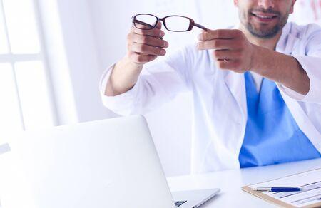 Portret mężczyzny lekarza z laptopem siedzi przy biurku w gabinecie lekarskim.