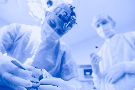 Man surgeon at work in operating room.